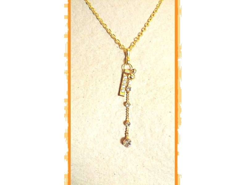 Gold chain rhinestone pendant necklace very glamorous and a gold rhinestone metal charm with a gold rhinestone-plated charm
