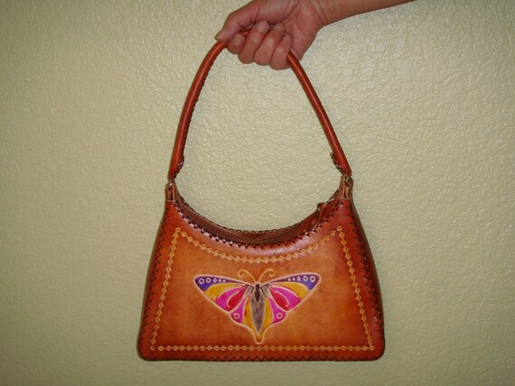 Genuine leather handbag with a leather piece Flower ornament on the front DarkOrange base and well made.