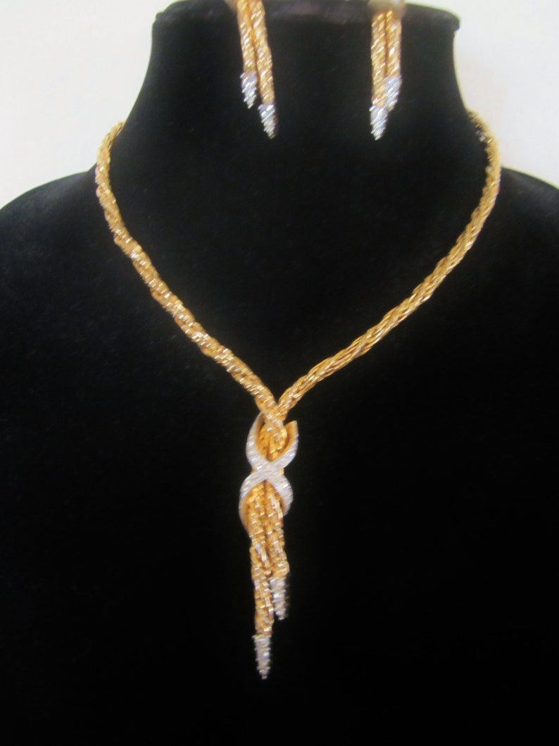 Gold-tone Art Deco-Style Necklace And Clip-On Earring Set crystal rhinestone accents 2 strands slip through a rhinestone-studded slipknot.