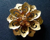 Vintage Designer Gardenia Style Gold Tone Floral Brooch Featuring Amber Colored Rhinestone Accents