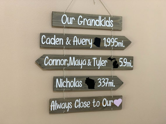 Grandkids sign with names, state maps and mileages. Grand kids directional sign wood on rope