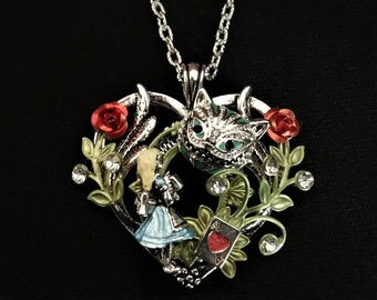 Hand-painted Alice in Wonderland-inspired heart-shaped pendant necklace with Alice, the Cheshire Cat, and Ace of Hearts playing card charms