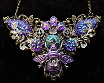 Stunning iridescent Steampunk Fantasy Queen Bee Necklace in purple pink and blue tones with clockface, flowers diamante rhinestone crystals