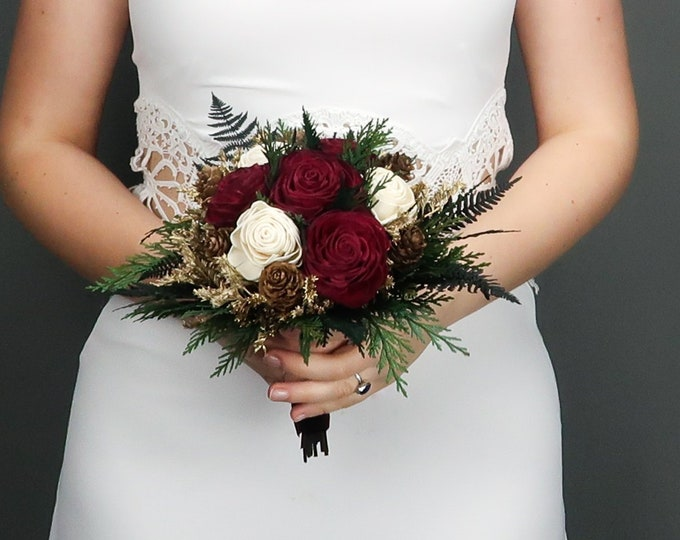 Small winter wedding bridesmaid bridal bouquet with burgundy and ivory sola roses, pine cones, gold dried flowers and preserved greenery