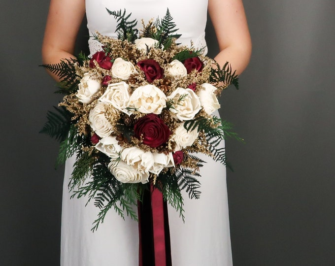 Teardrop winter wedding bridal bouquet with burgundy and ivory sola flowers, pine cones, gold dried flowers and preserved woodland greenery
