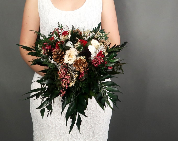 Cascading winter wedding bridal bouquet with pine cones, berries and real roses in red, burgundy, white, champagne