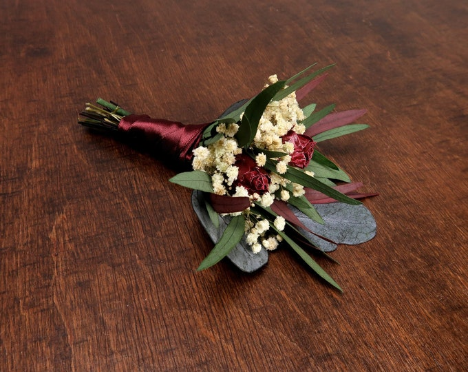 Wedding boutonniere with real burgundy roses, preserved flowers eucalyptus greenery, elegant boho style, realistic flower buds