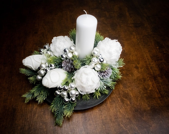 White glitter frozen snow winter wedding Christmas dinner table centerpiece with a candle, artificial fir, glass ornaments floral decor