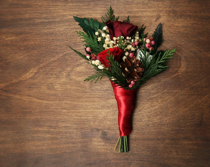 Winter wedding groom boutonniere with pine cones and real preserved roses in red burgundy white