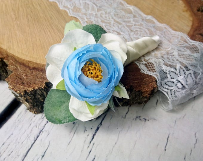 Wedding boutonniere with pastel blue peony, white hydrangea and greenery