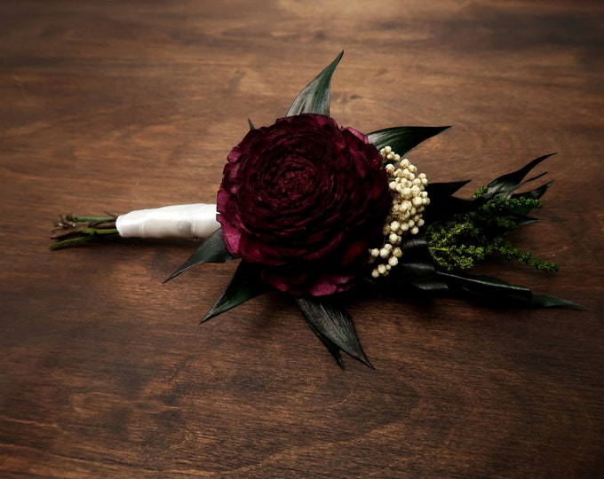 Sola flower wedding boutonniere in shades of dark wine and green
