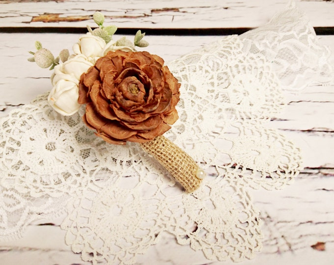 Wedding boutonniere with natural brown cedar rose, ivory sola flowers and artificial eucalyptus