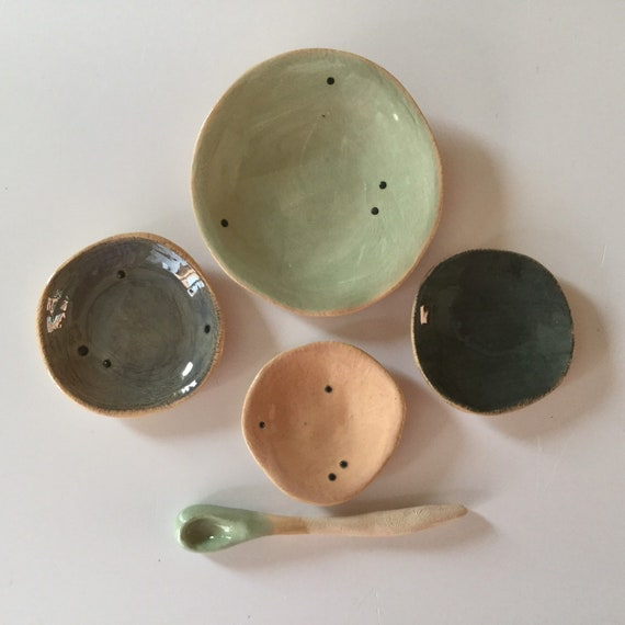 Four tiny stacking plates with spoon