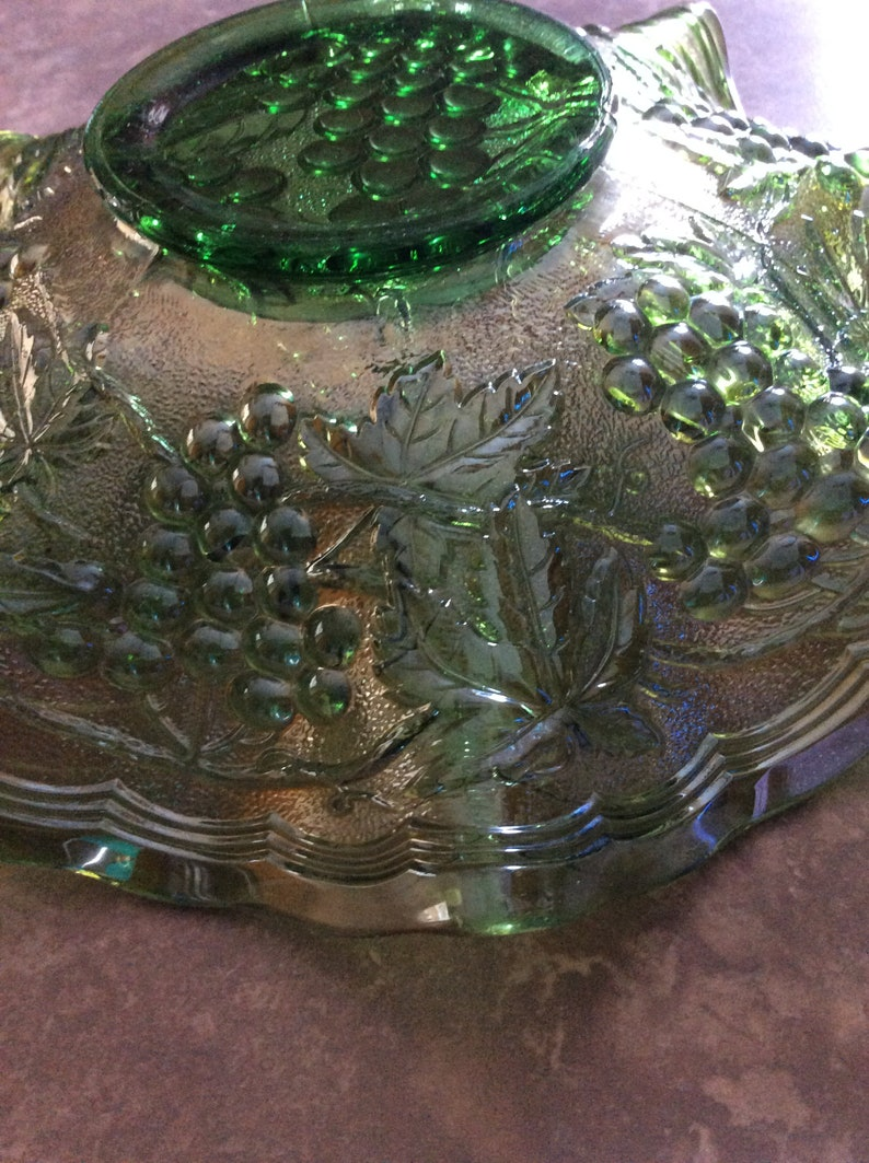 A beautiful Helios green iridescent carnival ruffled glass dish with a raised grape and leaf design Fenton.