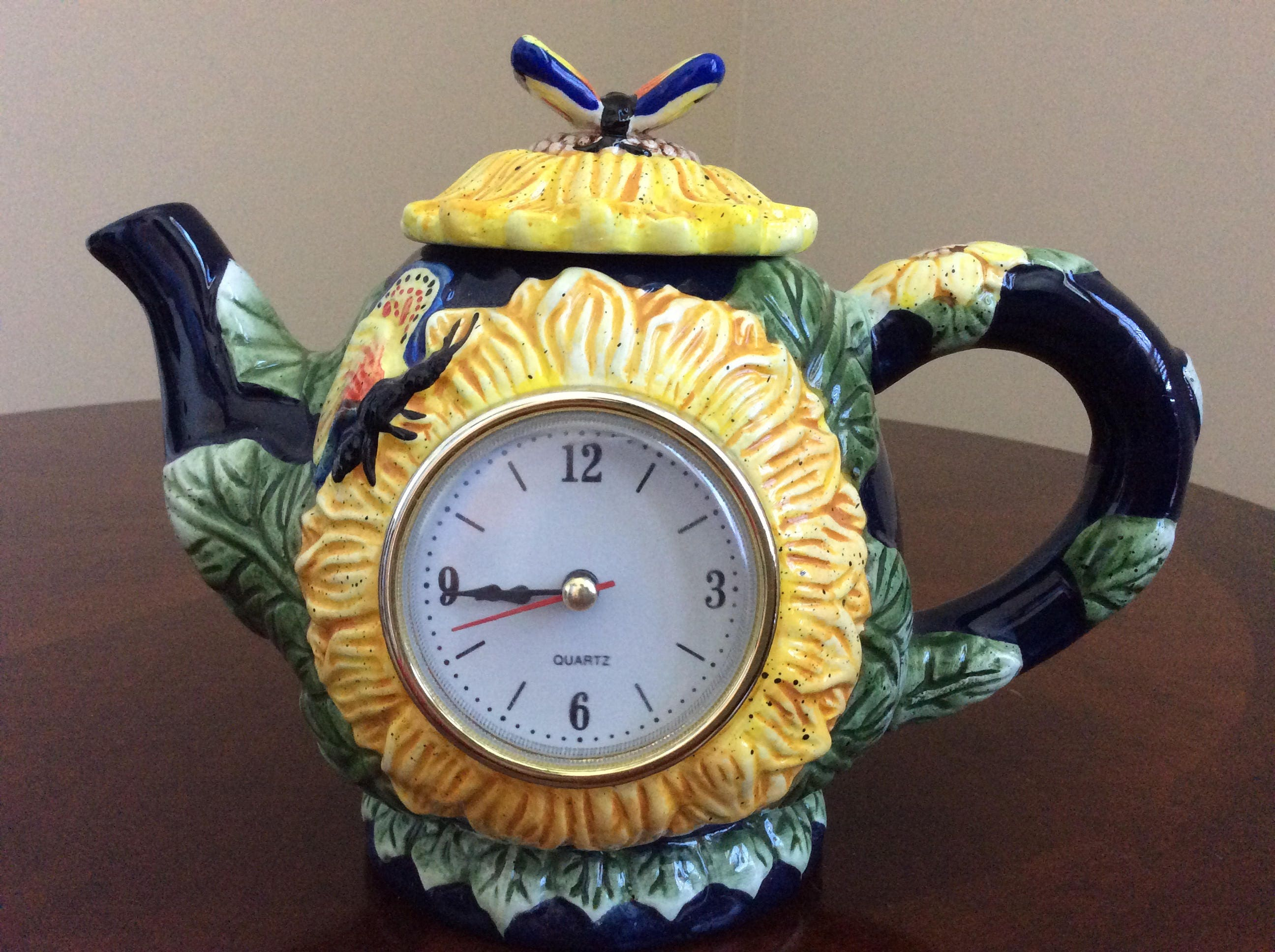 A Decorative Teapot Clock With Lid Sunflowers And