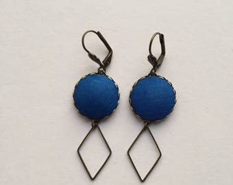 brass earrings and blue fabric