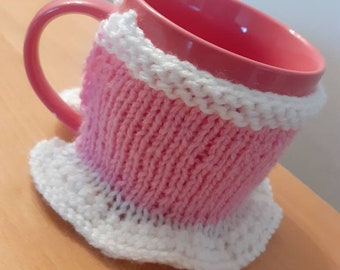 Hand knitted mug cosy with frilly skirt suitable for a small/medium mug