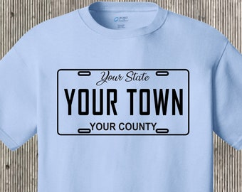 Your town (community, city, etc) license plate car tag T shirt also featuring your state and county - any place!  Many colors to choose from
