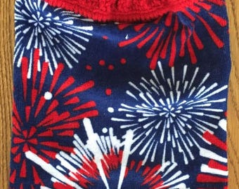 Hanging kitchen towel with a crocheted top.  The pattern shows bright fireworks display in red and white on navy blue. The tab is in red.