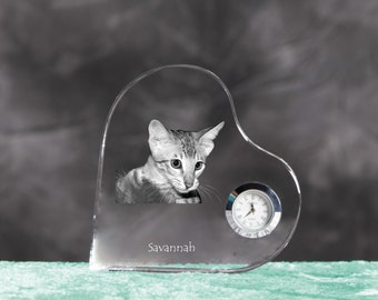 Savannah cat- crystal clock in the shape of a heart with the image of a pure-bred cat.