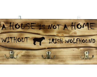 """Irish Wolfhound, a wooden wall peg, hanger with the picture of a dog and the words: """"A house is not a home without..."""""""