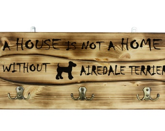 """Airedale Terrier, a wooden wall peg, hanger with the picture of a dog and the words: """"A house is not a home without..."""""""