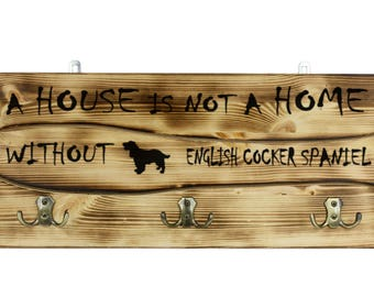 "English Cocker Spaniel, a wooden wall peg, hanger with the picture of a dog and the words: ""A house is not a home without..."""