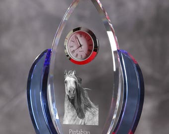 Pintabian-   crystal clock in the shape of a wings with the image of a pure-bred horse.