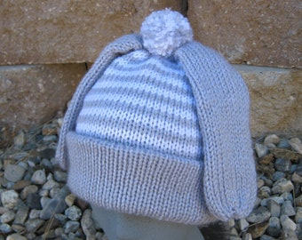 4e901b2751f Hand knit child s hat is gray and white stripes with bunny ears and a pom  pom tail.