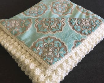 Pale teal and gray fabric-lined crocheted baby blanket
