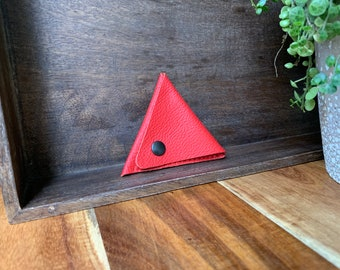 Leather triangle coin purse made of thin red leather.