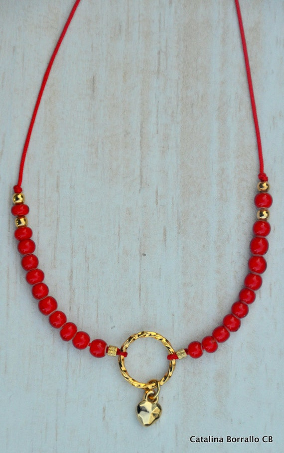 Necklace of red beads with gold and heart ring