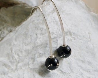 Sterling earrings with black Oltu stones with inlaid silver dots.