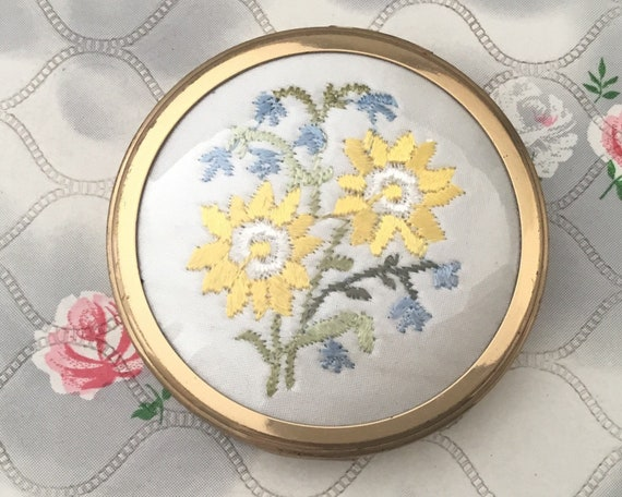 Margaret Rose creme powder compact with yellow sun flowers embroidery, gold tone makeup mirror c1960s or 1970s