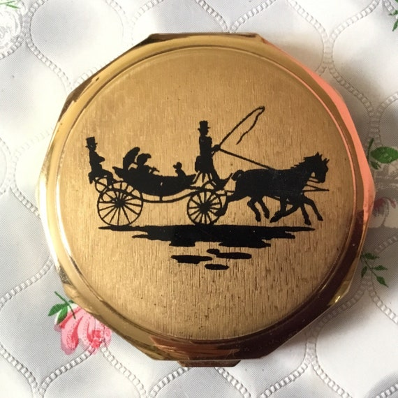 Vintage Stratton powder compact mirror, circa 1960s or 1970s.  This decagon compact is gold tone, with a horse and carriage design.