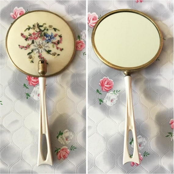 Magnifying makeup mirror with petit point embroidery, c 1950s floral vanity hand mirror