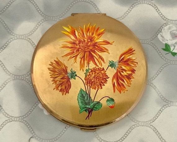 Vintage loose powder compact in hand, with orange chrysanthemums, 1950s floral compact