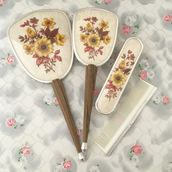 Vintage 3 piece brush set comprises of a hand mirror, hairbrush and clothes brush.  This yellow floral dressing table set is c1960s or 1970s