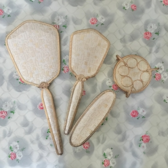 Regent of London hand mirror, hairbrush, lipstick holder and clothes brush set, c1950s or 1960s gold lamé vintage vanity set