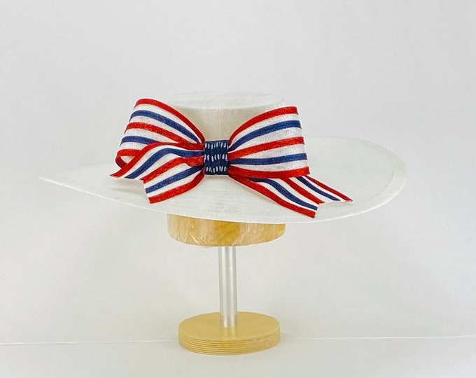 White hat with red, white and blue bow