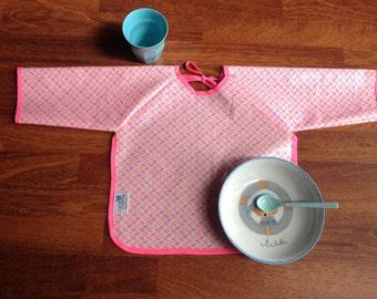 Bavoir à manches en coton enduit Petit Pan aux motifs Momoyo rose fluo, bleu turquoise et jaune