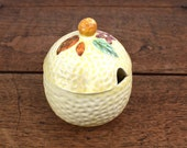 Vintage sugar bowl or jam pot, dimpled glaze ceramic with fruit and flower decoration on the lid