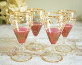 Four vintage sherry glasses, opulent ruby red and gold with clear glass stems.