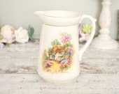 Vintage milk jug or pitcher, cream ceramic with pink and green cute vintage cottage garden scene design.