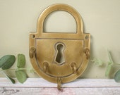 vintage brass wall hooks, four key hooks, on a large padlock shaped base