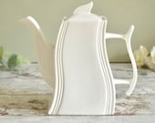 White ceramic teapot in unusual curved wave shape
