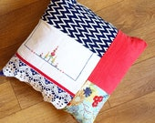 Patchwork cushion or pillow created from red, white and blue cottons including up-cycled and vintage linens