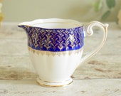 Small milk/cream jug with royal blue rim gilded with pretty sprig floral design, vintage English bone china