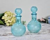 Pair of turquoise blue vintage pressed glass bottles with stoppers