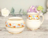 Cream ceramic sugar bowl and creamer set, Sadler 1930's orange and blue pattern.